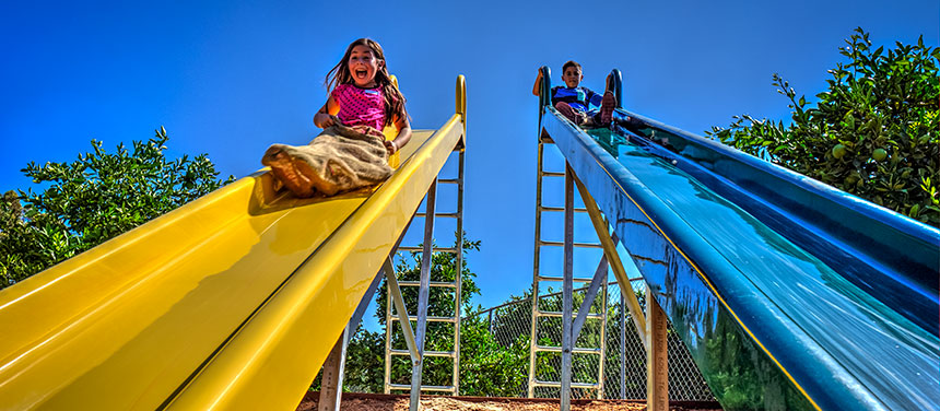 Two childen playing on a slide
